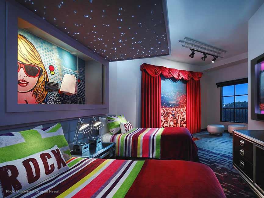 Cuarto de 2 camas queen con acolchado rojo y rayas de colores